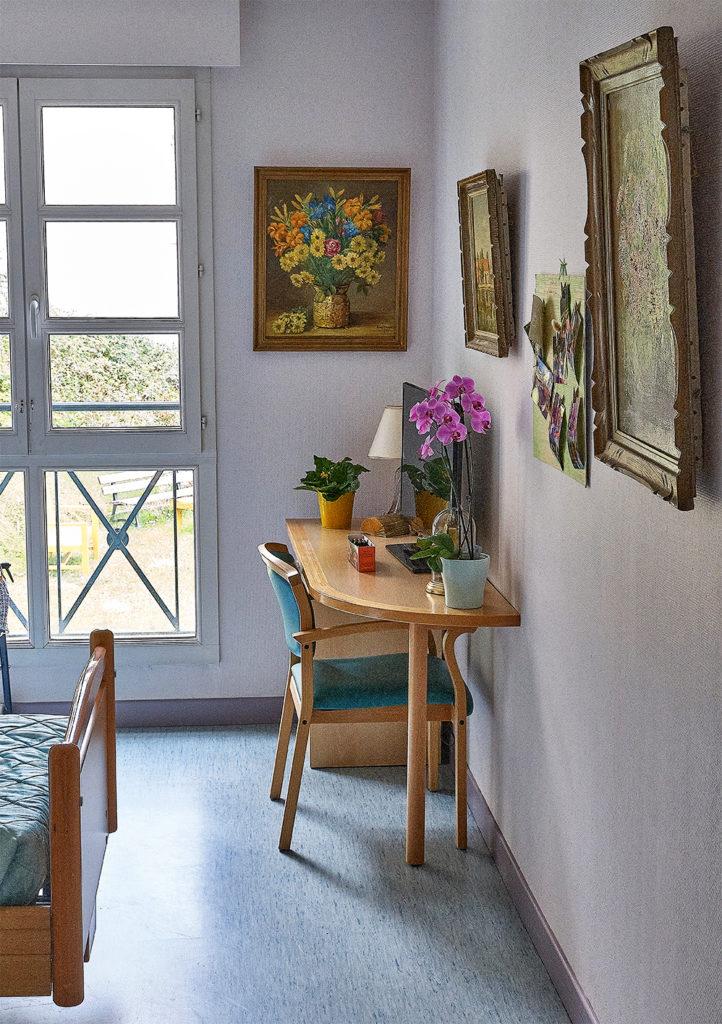 Photo d'une chambre d'un résident avec tableaux au mur